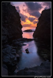 Intense sunset color as seen between two rocks along the north shore of Kauai