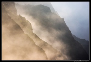 Heavy sea mist hugs the Na Pali coast as the setting sun illuminates it along the cliffs.